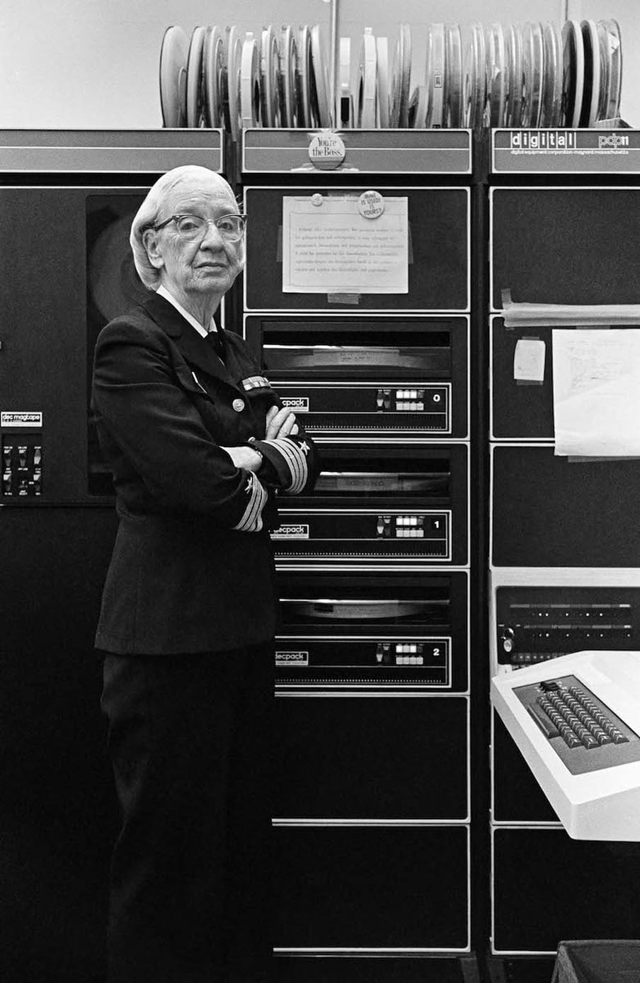 Black and white photograph of a woman with glasses wearing a US Navy suit, standing next to a computer.