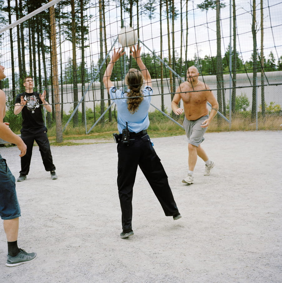 Four figures playing volleyball, central figure wears a prison guard outfit and jumps to reach the ball, the net runs through the picture. To the left is a figure in black with hands rising up, to the right a topless man in shorts and trainers running towards the ball