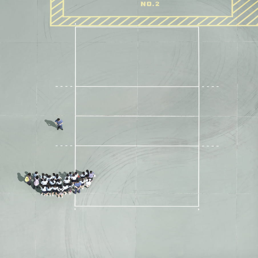 Aereal photograph on what looks like a mint green clay court with white and yellow box markings in the ground. To the bottom centre left, we see the heads and backs of a group of people gathered in a semi-circle, to have their picture taken by a photographer.