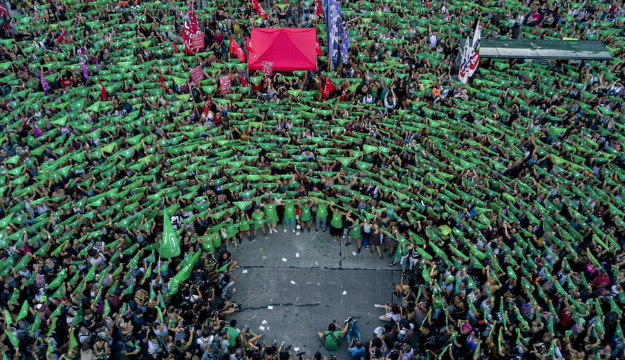 Photo of a crowd of people from above, all holding up a green bandana. There's a hole in the crowd at the bottom, where photographers sit