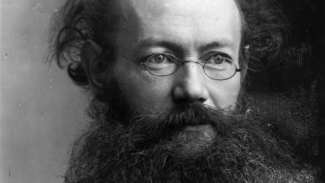 Black and white archival photographic portrait of a bolding man with a beard and glasses.