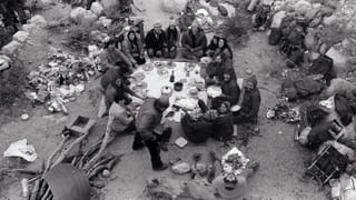 Black and white photo of a group of people sit on the floor in nature, having a picnic