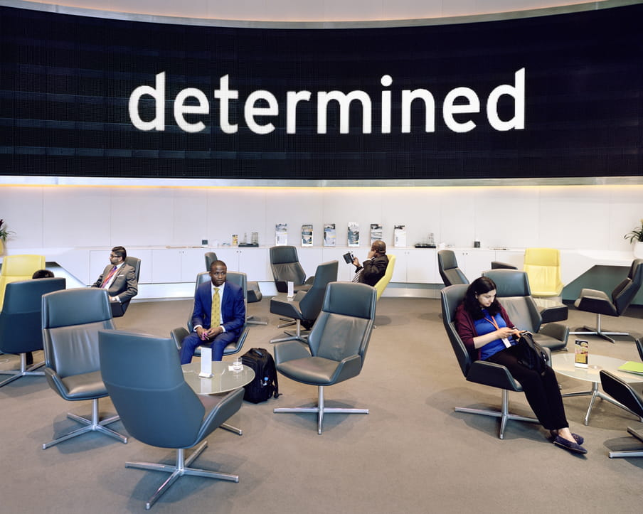 Photo of a lounge with people in comfortable chairs, the word 'determined' on a large screen in the back