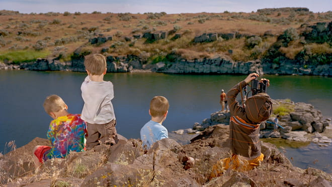 Photo of children playing outside: we see them from the back, one is looking up with binoculars