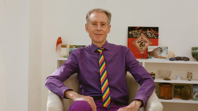 Centre of photo is a person sitting in cream coloured armchair, dressed in purple shirt and trousers, with a stripy red, blue and yellow tie, and with shirt grey hair, hands resting on lap, arms at angles on armrests. Behind is a white bookcase with various objects, including small flags, pots and sunglasses.
