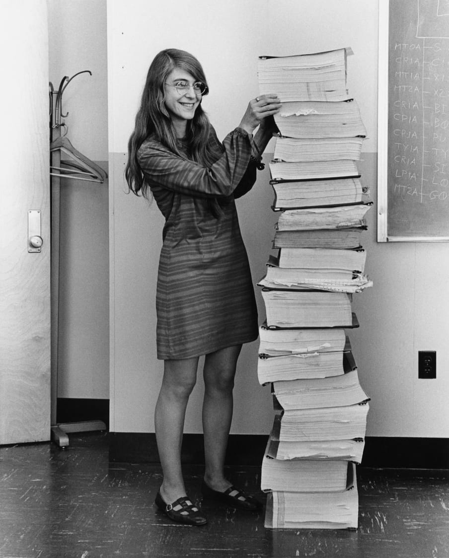 Black and white photograph of a woman wearing glasses, smiling, standing next to a pile of document as tall as her.