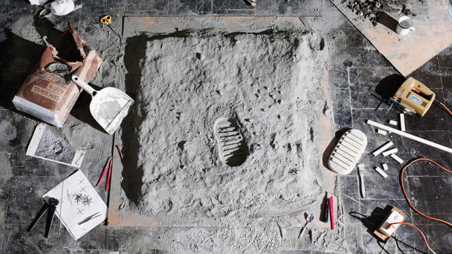 Dioramas of boot footstep in the mud, in a photo studio, with props laying around.
