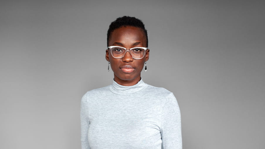 Photographic portrait of a woman with glassed, a turtleneck sweater and earrings - OluTimehin Adegbeye - against a grey background.