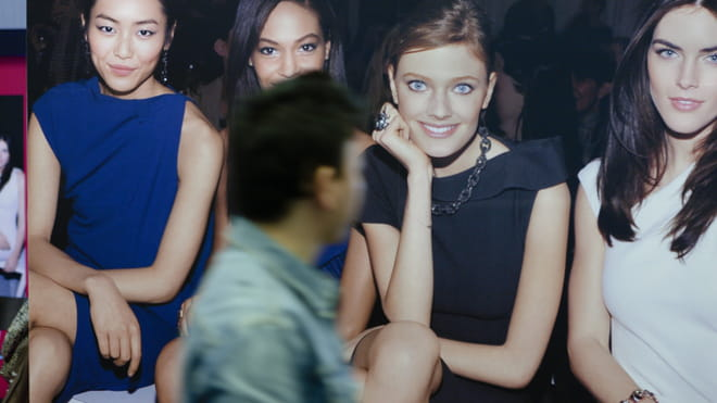 Photograph of a man, blurry, looking at what seems to be a poster of four smiling and stylish women sitting.