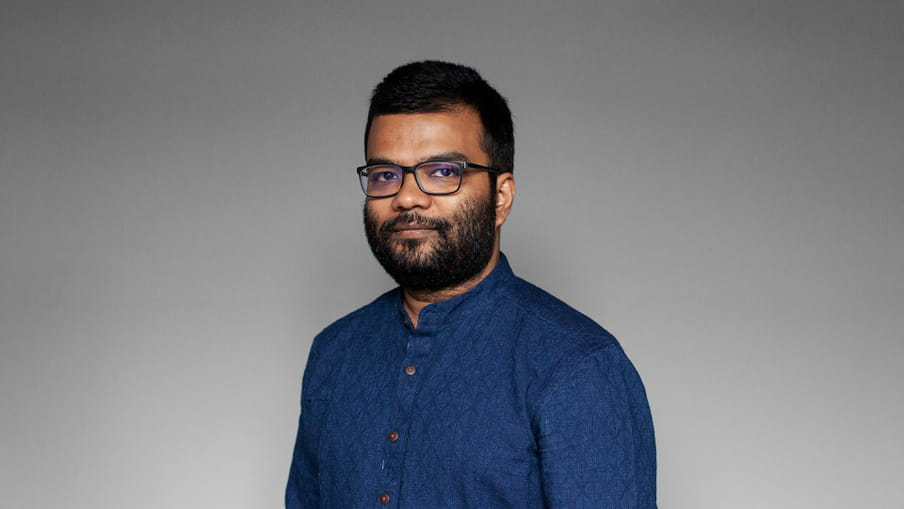Photo of a man with a beard and glasses - Tanmoy Goswami - against a grey background.