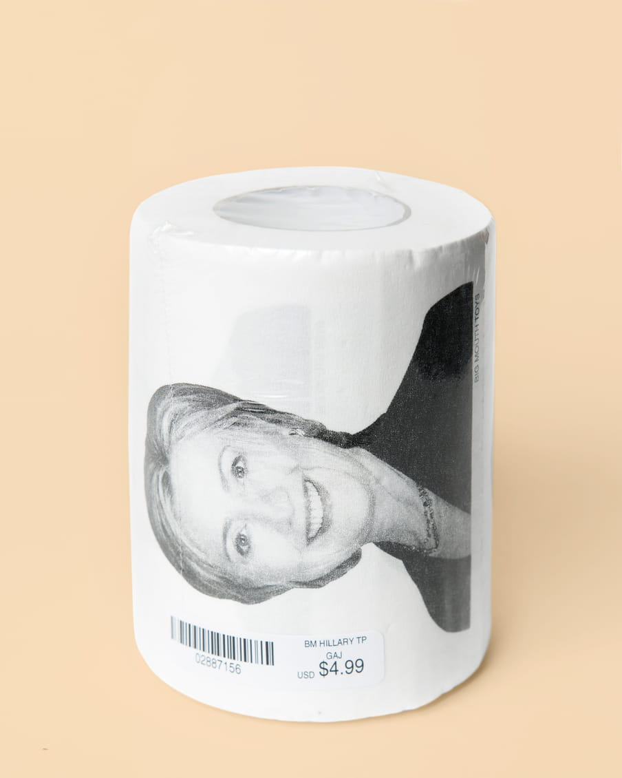 Photo of a roll of toilet paper with a picture of Hillary Clinton on it - on a pink background