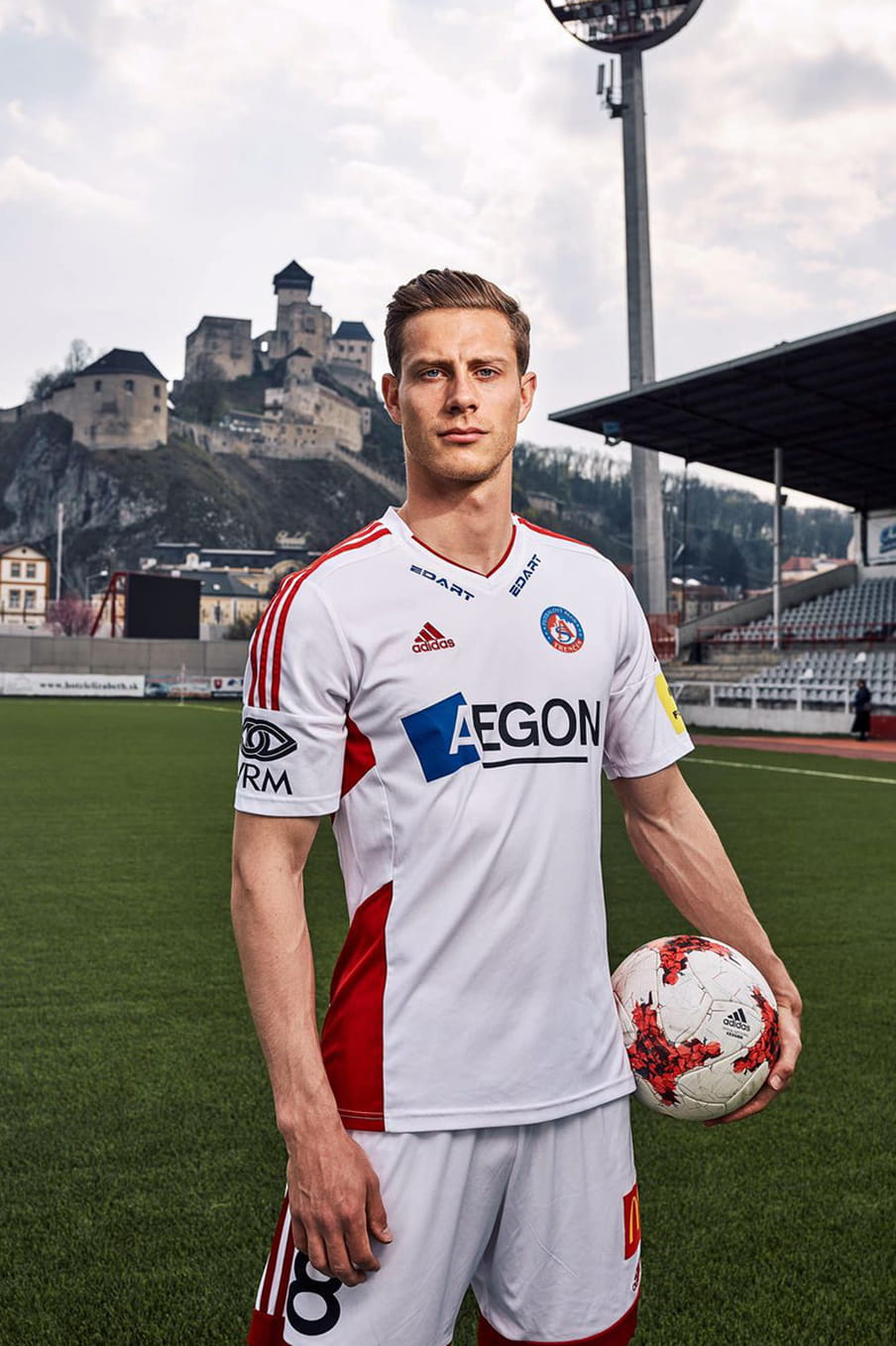 James Lawrence on the pitch of Slovenian football  club Tencin, posing for the camera with a ball loosely in his left hand. In the background a small castle on a hill top can be seen overlooking the stadium.
