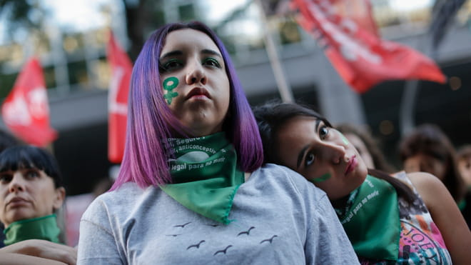 Photo of two girls at a demonstration, one with dark hair and one with purple hair, both wearing green bandanas around their neck