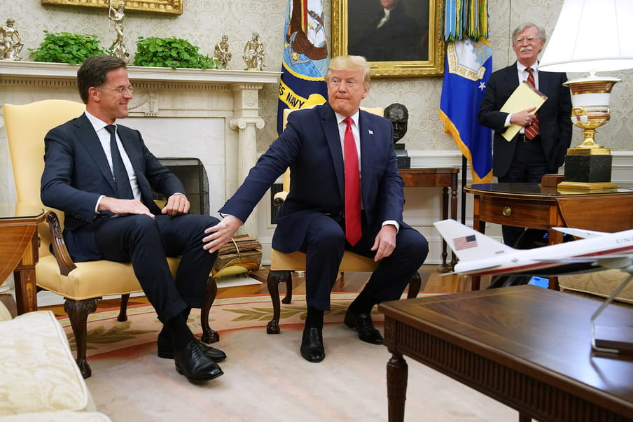 Two men wearing suits are sitting in yellow chairs. One man is touching the other man knee. The man who is touched is smiling. In the back, a third man is standing, also smiling.