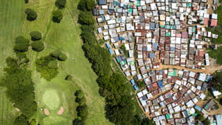 Drone photo of a land. On the right a shanty town, on the left a residential aerea.