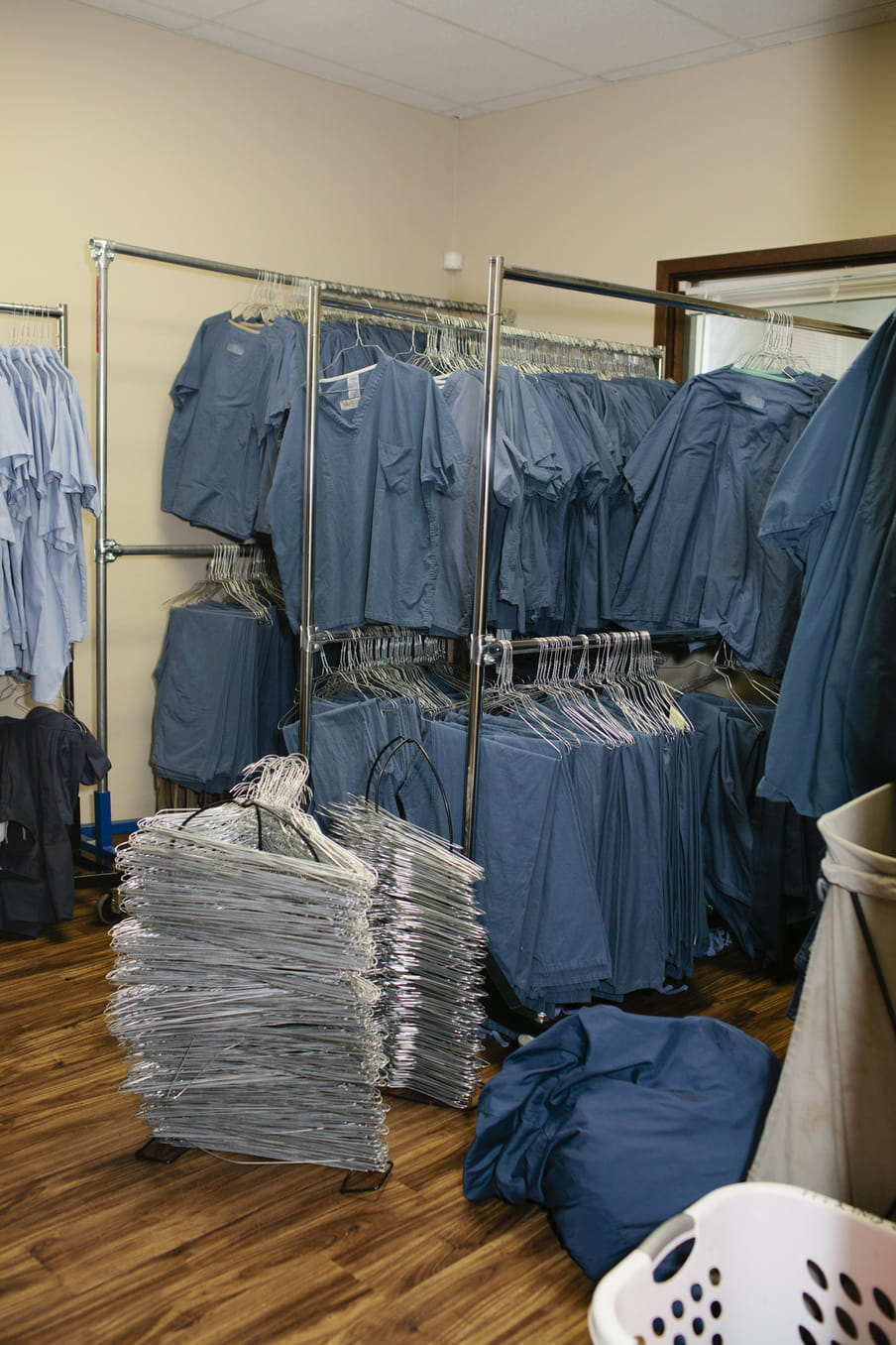 A photo taken in a room with four metal rails, filled with hanging blue smock uniforms worn by employees. At the front right, we see a white wash basket, a blue bag, and tall columns of silver metal hangers on the floor.