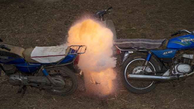 The ground is grassy with brown straw, upon which we see two blue Suzuki motorbikes, both not fully in shot. Where they touch, there is a fire which looks like it has just combusted