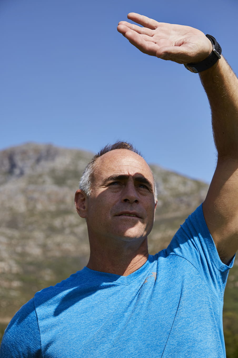 Photo of a man in a blue shirt looking up, blocking his eyes from the sun with his arm