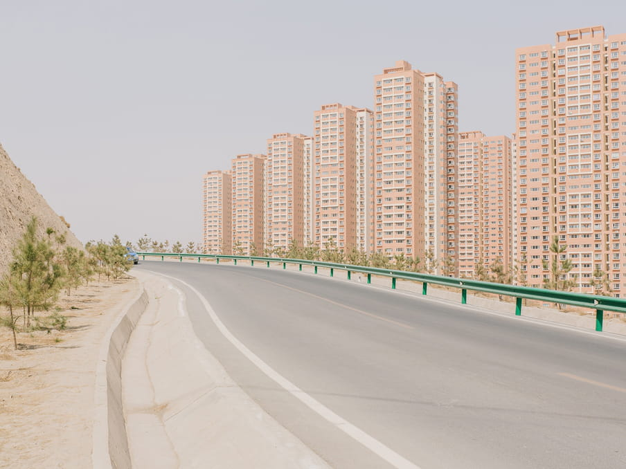photo of a road next to some buildings and a car approaching