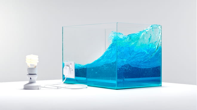 Photo of a lamp connected to a tank of water with a wave in it, the lamp is on