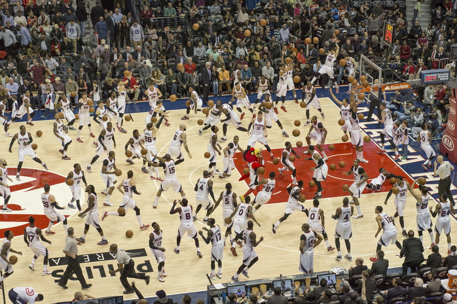 Photo-montage of a basketball field, heavily crowded with men playing.