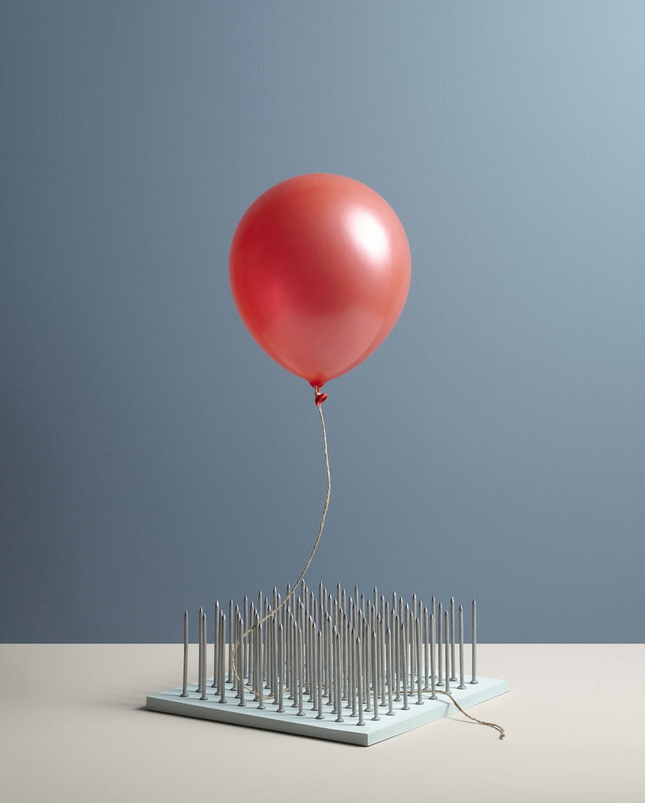 Colour photograph of a red ballon floating over a bed of nails.