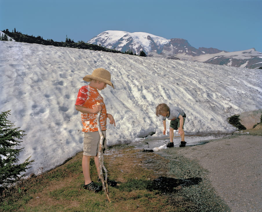Photo of two boys playing, a mountain full of snow behind them