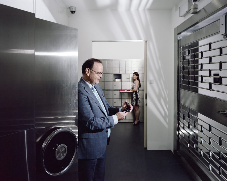 Man looking at a diamond while standing in front of a large safe. A woman standing in the back, looking at him.