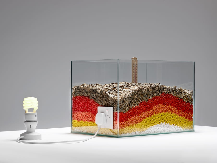 Photo of a lit lamp connected to a glass tank, white, yellow orange, red and brown stones and a thermometer in it
