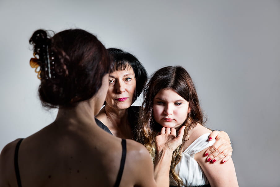 Photo of three humans figures: one is giving her back toward the camera and is caressing her daughter face. At the center, the grandmother hugging the granddaughter