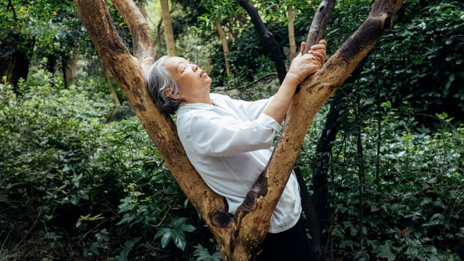 Elderly woman leaning on a tree branch with her eyes closed, the background filled with plants and trees