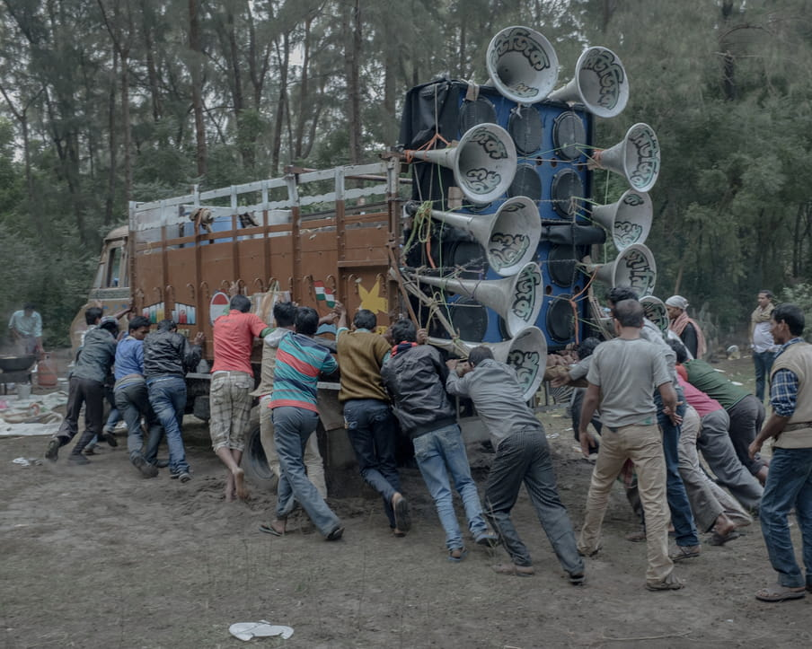 A group of men is pushing what seems to be a heavy truck filled with a elaborated sound system.