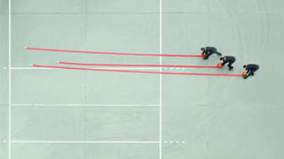 Photograph taken from above of three men unrolling red hoses on a mint green ground court.