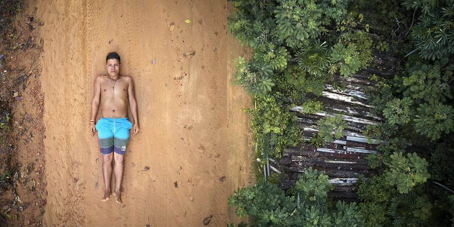 On the left, a human male figure lying on the ground, on the right an aereal pictures of the forest