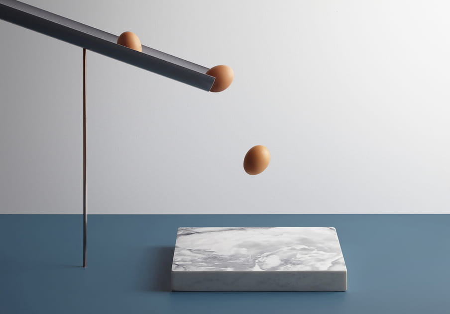 Colour photograph of a rock eggs about to fall on a piece of marble.