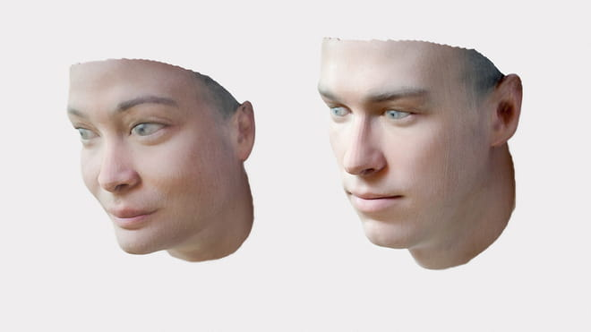 Photo of two 3D printed faces, of a woman and a man. They start at the neck and end at the top of the head, containing ears but no hair - on a white background