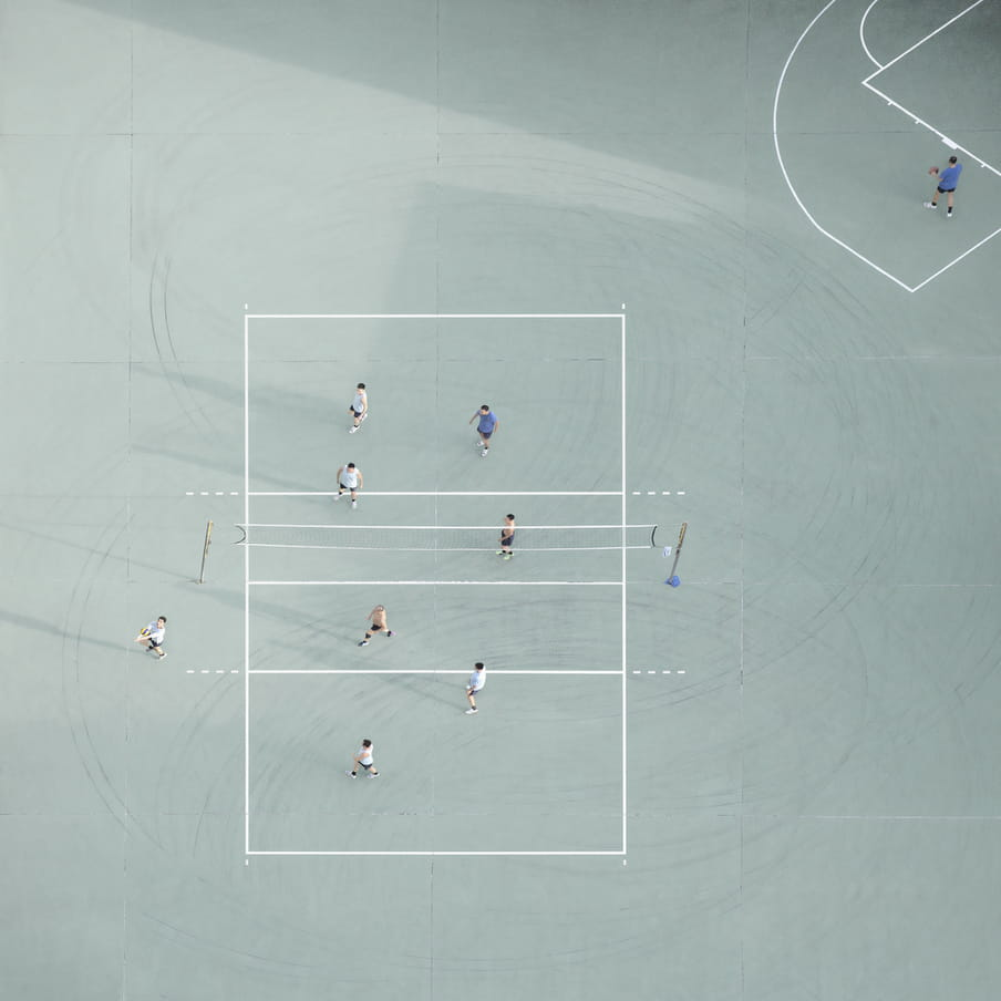 Photograph taken from above of men playing volleyball on a mint green court.