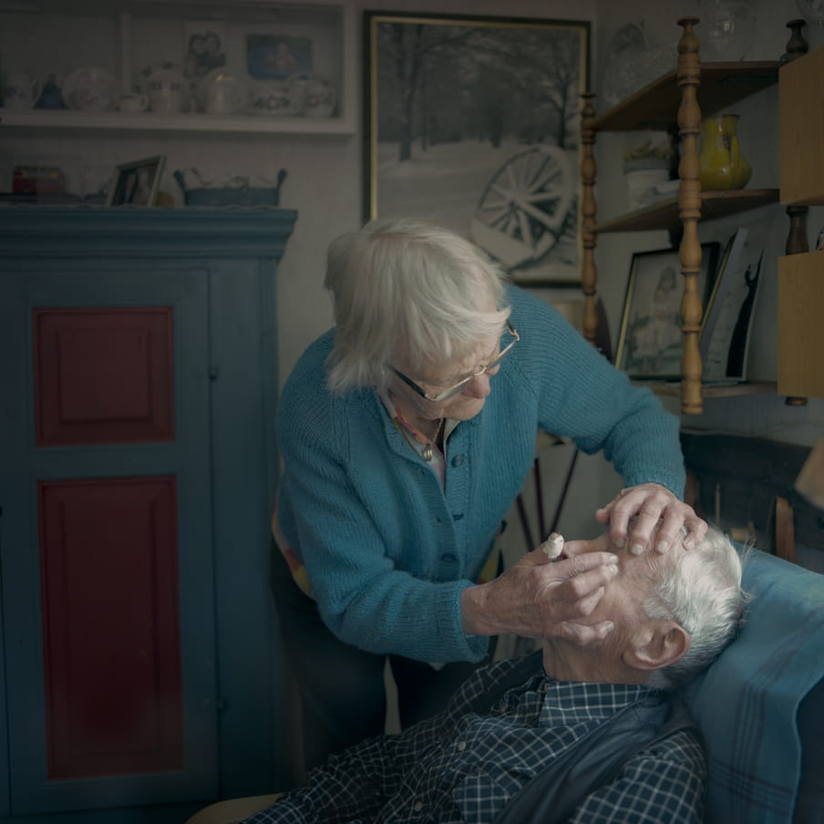 Photograph of an elderly couple. The man is sitting in a chair and the woman is bending over, appearing to get something out of the man his eye.