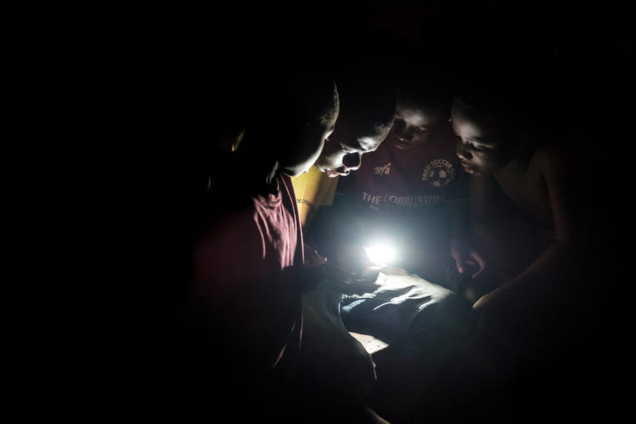 Four children are gathered around a luminous element, hold by a boy with a yellow top. They all look in the direction of the light.