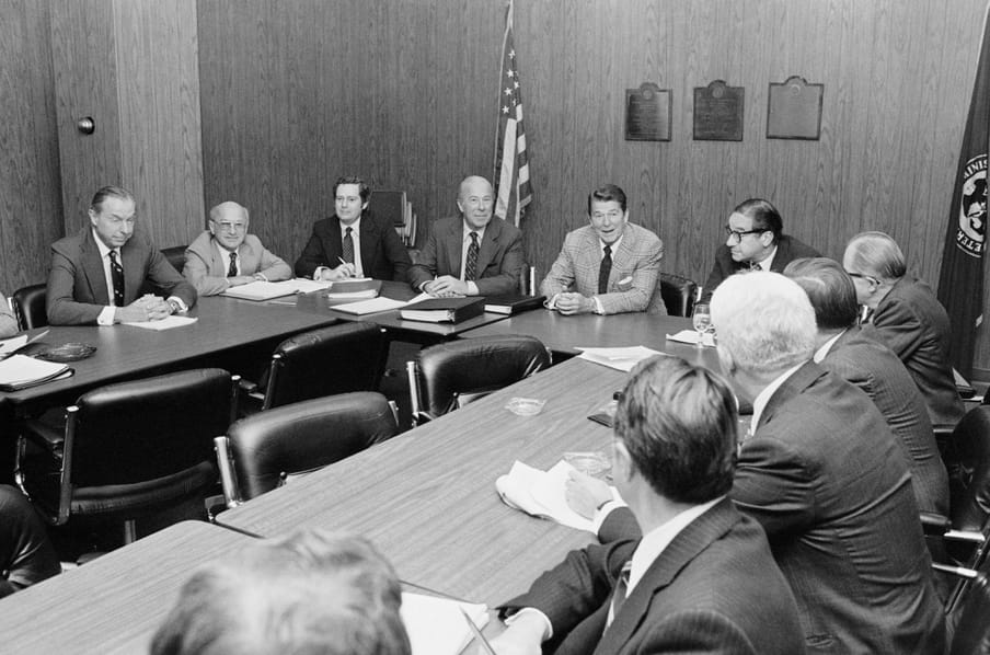 Table with 11 men in suits, american flag in the back