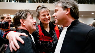 Photo of three people hugging