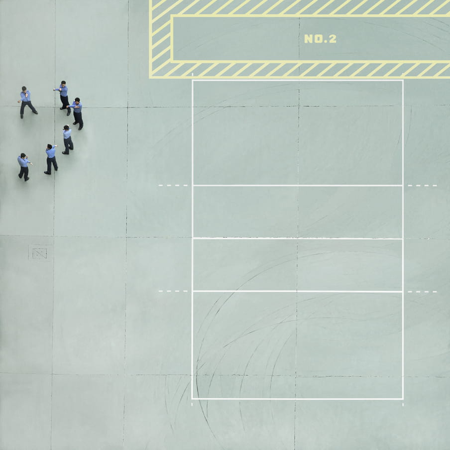 Photograph taken from above of men in blue shirts and black pants stretching on a mint green cour