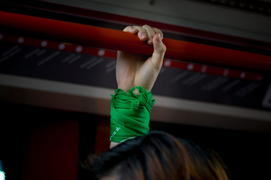 Photo of a hand with a green bandana holding a handle on a bus