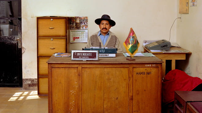 A Bolivian government worker with a black moustache sits behind a wooden desk. He's wearing a black hat and a light-blue shirt underneath a beige cardigan. A typewriter, a plate with his name and job function and a small Bolivian flag are placed in front of him. Some documents are lying on his desk. Behind him is a chest of lockable office drawers and another small table with a fax machine. A calendar is fastened to the wall. Two wooden chairs are visible on the side in front of the large desk.