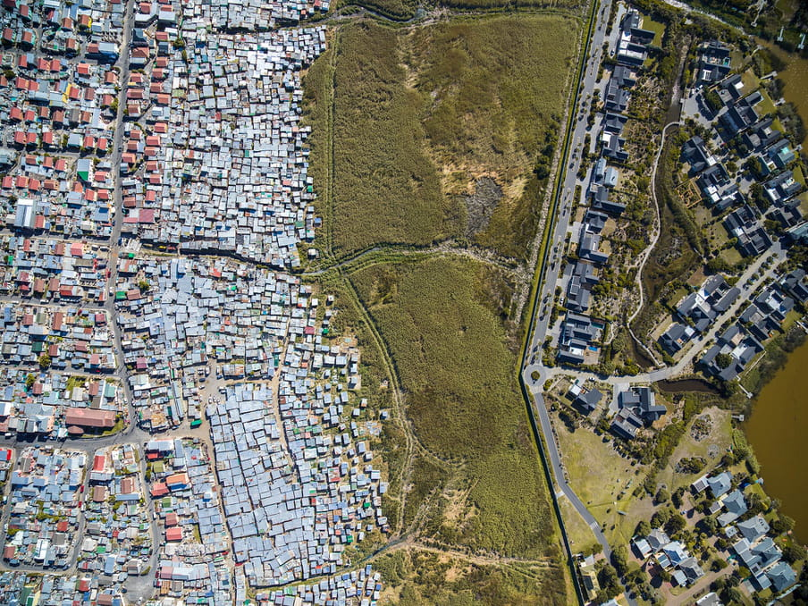 Drone photo of a land. On the left a shanty town, on the right a residential aerea.