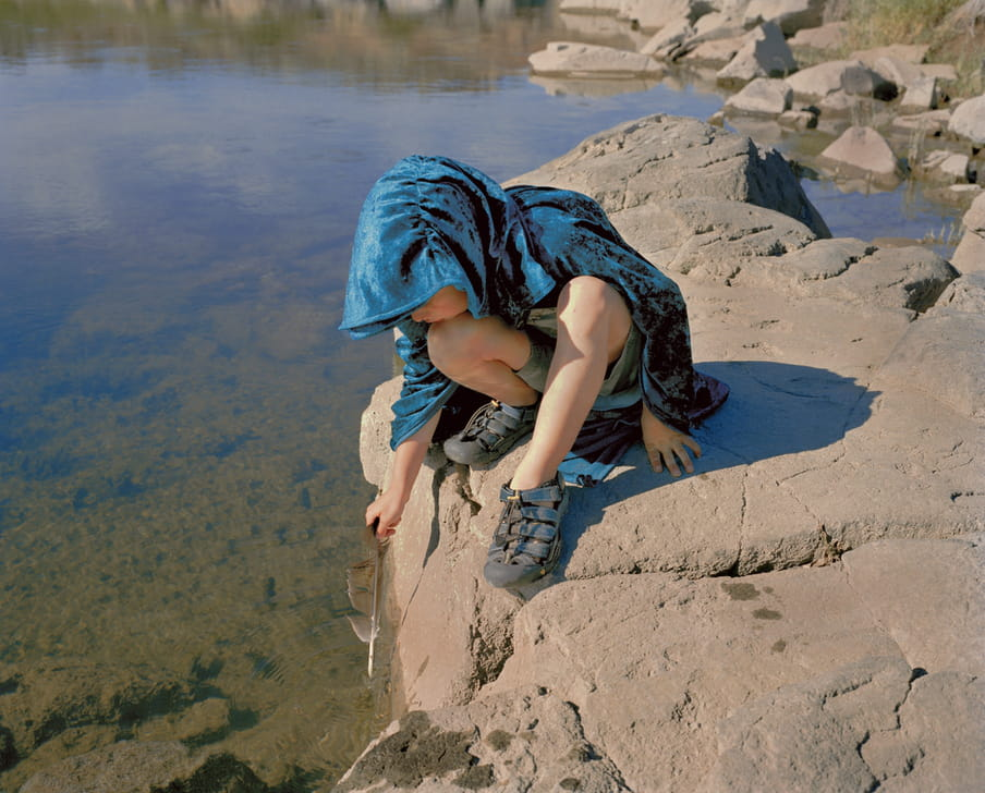 Photo of a boy playing with a feather at a river side