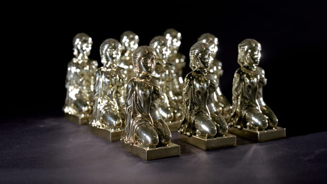 Photo of nine similar silver statues of a woman sitting on her knees with her hands on her back