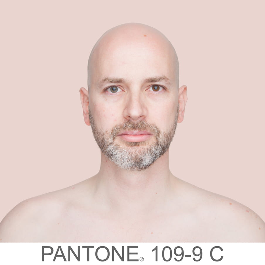 Photographic portrait of a bold man with a beard. The background is a sample of 11 x 11 pixels taken from the nose of the subject and matched with the industrial pallet Pantone®. The pantone color is written out as PANTONE 109-9C.