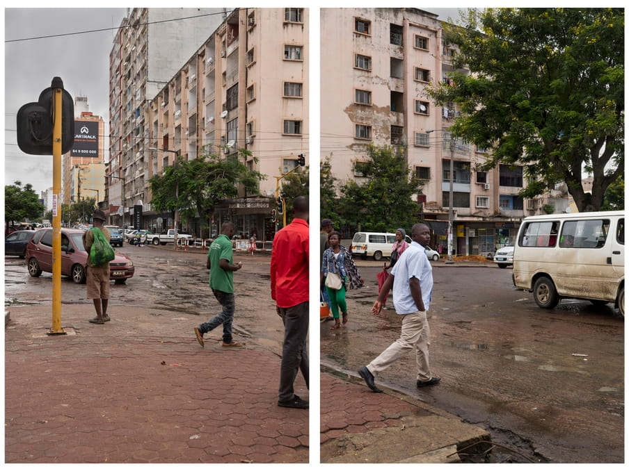 An image of people crossing the road. In the background a decaying building and trees lining the sidewalk.