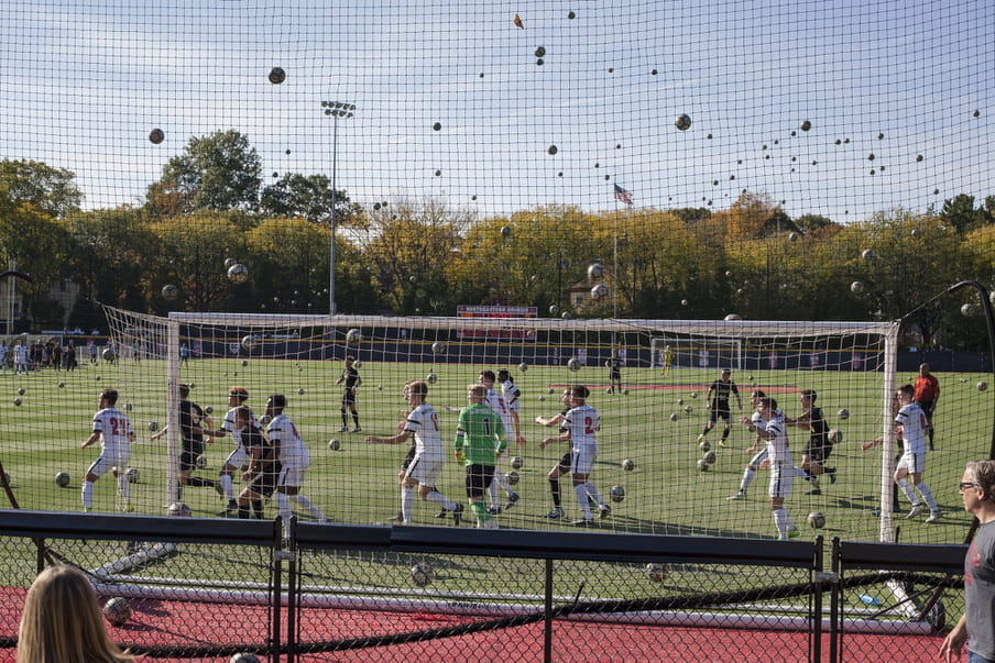 Photo-montage of a soccer field, heavily crowded with men playing.